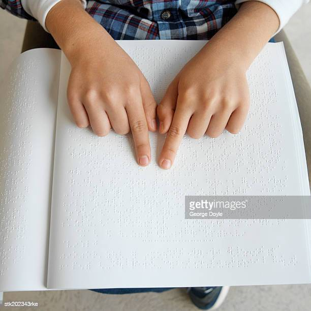 elevated view of the mid section of a person reading by Braille