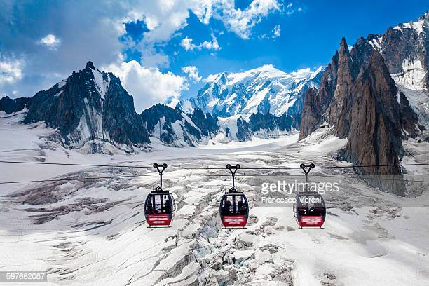 Elevated view of three cable cars over snow covered valley at Mont blanc, France