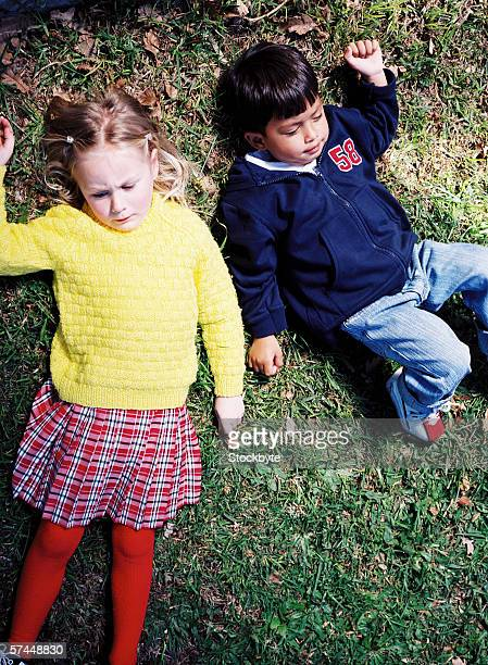 Elevated view of two young children (4-8) lying on the grass