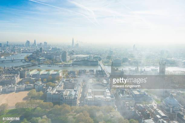 Elevated view of Westminster, the London Eye, and river Thames in mist