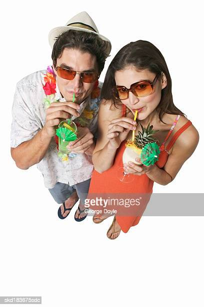 Elevated view of young couple drinking glasses of cocktails