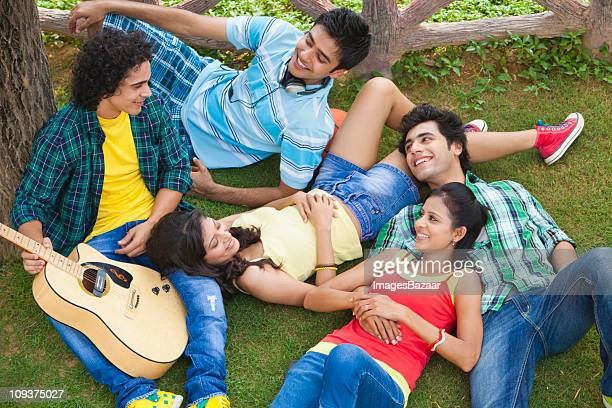 Elevated view of young people with guitar relaxing on grass