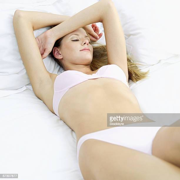Elevated view of young woman lying on a bed wearing lingerie