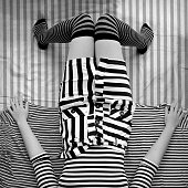 Elevated view of young woman wearing striped clothes, lying on bed
