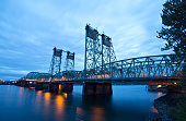 Long metal truss arch bridge with green lifting hoist on high rack in the middle of the Columbia River in the evening with the lights of passing cars on the bridge reflected in the water of the river.