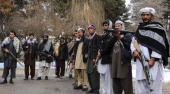 Eleven former Taliban fighters carry their weapons during a handover as they join a government peace and reconciliation process at a ceremony in...