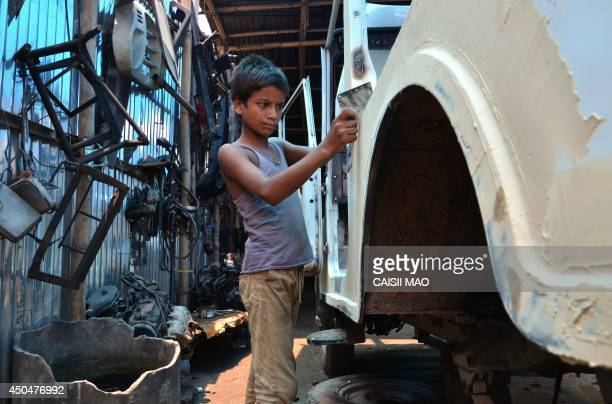 Eleven yearold Indian boy Mohammad Abdul Salem works on a car at a vehicle repair garage on World Day Against Child Labour in Dimapur in northeastern...