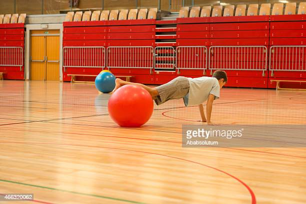 Onze anos velho Menino brincando com bolas de Fitness ginásio, aulas