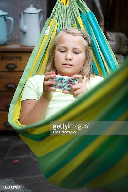 Eleven years old girl laying in a hammock playing with her cellphone on August 10 2015 in Bonn Germany