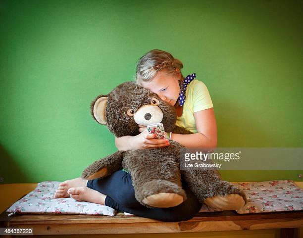 Eleven years old girl with a huge teddybear and her cellphone on August 10 2015 in Bonn Germany