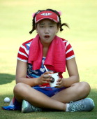 Elevenyear old Amateur Lucy Li of the United States takes a break as she waits to hit on the third hole during the first round of the 69th US Women's...