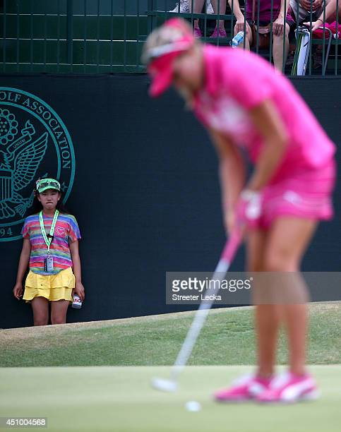 Elevenyear old Amateur Lucy Li of the United States watches as Lexi Thompson of the United States putts on the 13th green during the third round of...