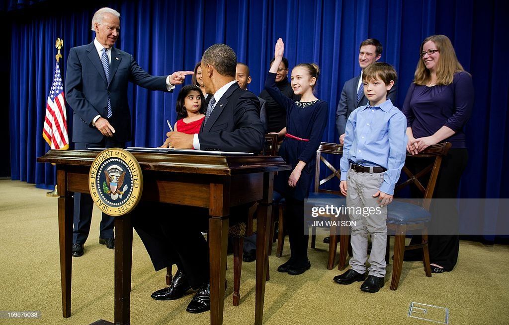 Eleven-year-old Julia Stokes, who wrote a letter to the White House, raises her hand as US President Barack Obama (C) asks if anyone else is left handed as he signs executive orders during an event unveiling a package of proposals to reduce gun violence at the White House in Washington, DC, January 16, 2013. US President Barack Obama signed 23 executive orders to curb gun violence and demanded Congress pass as assault weapons ban, in a sweeping set of measures in response to the Newtown massacre. AFP Photo/Jim WATSON