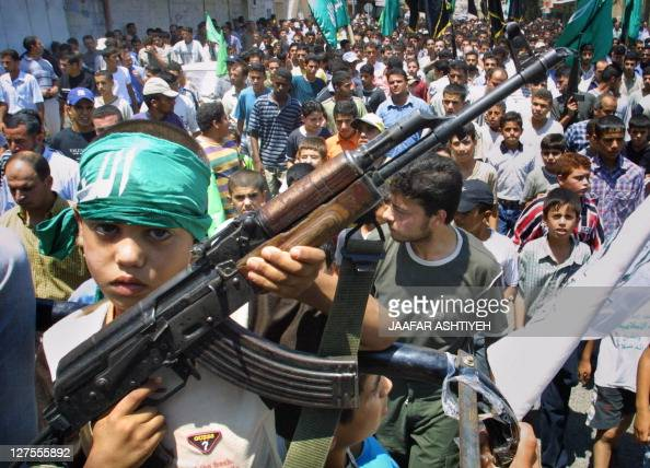 Elevenyearold Mosaeb the son of Hamas movement member Mahmud Mussa Suleiman carries a Kalashnikov during a march in the center of West Bank town of...