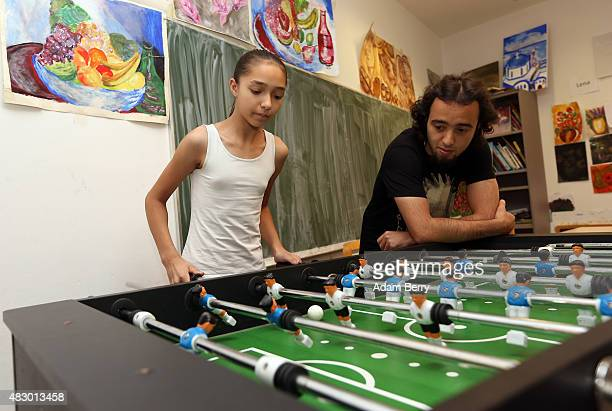 Elevenyearold Serbian refugee Kristina plays table football or foosball with Iranian refugee Andabili Hossein at a temporary home providing...