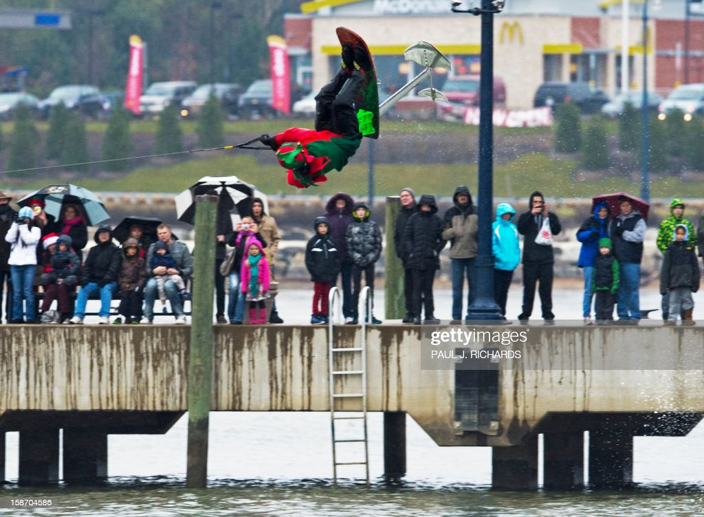 A Elf on a ski-chair does a flip on the chilly Potomac River near Washington, DC, December 24, 2012, at National Harbor in Maryland. The free show is put on every Christmas Eve with a water skiing Santa Claus, Elves, and Reindeer. AFP PHOTO/Paul J. Richards