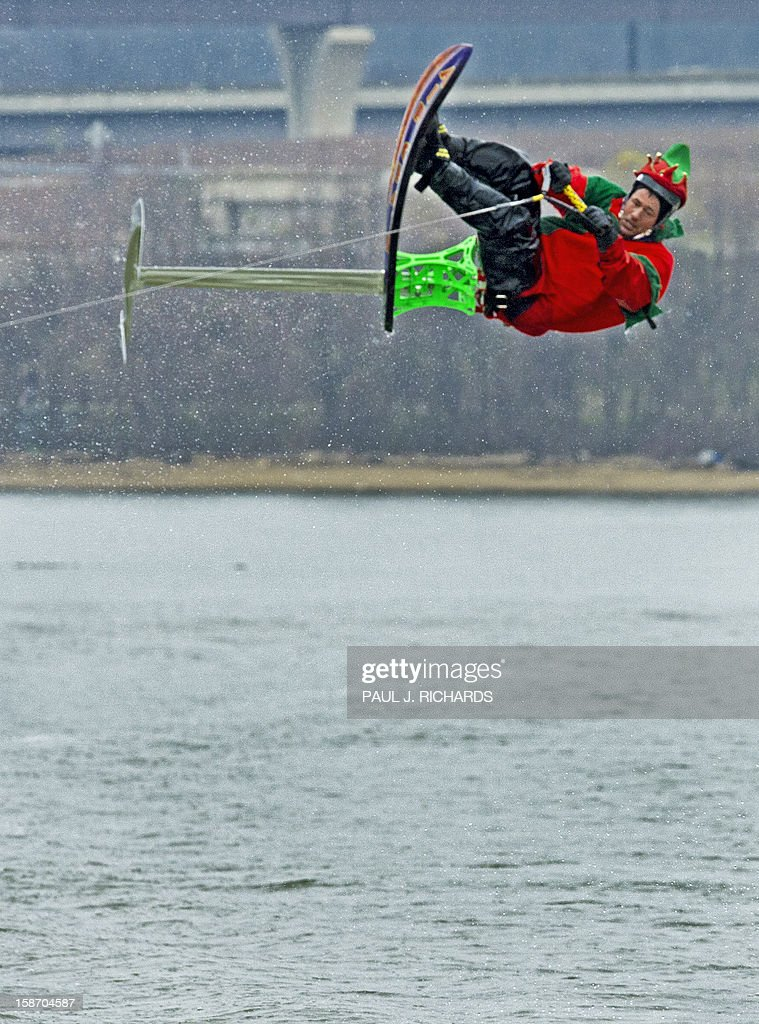 A Elf on a ski-chair rids on the chilly Potomac River near Washington, DC, December 24, 2012, at National Harbor in Maryland. The free show is put on every Christmas Eve with a water skiing Santa Claus, Elves, and Reindeer. AFP PHOTO/Paul J. Richards