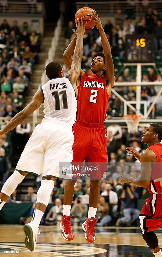 Elfrid Payton #2 of the Louisiana-Lafayette Ragin' Cajuns takes a three pointer to try and tie the game with 1.5 seconds left behind Keith Appling #11 of the Michigan State Spartans at the Jack T. Breslin Student Events Center on November 25, 2012 in East Lansing, Michigan. Michigan State won the game 63-60.