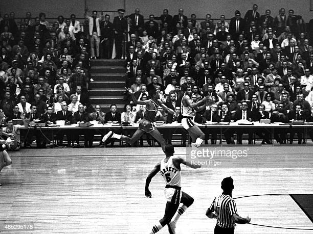 Elgin Baylor of the Los Angeles Lakers looks to pass as Bill Russell of the Boston Celtics goes for the block as Dick Barnett of the Lakers looks on...