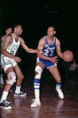 Elgin Baylor of the Los Angeles Lakers moves the ball against Sam Jones of the Boston Celtics during a game played in 1966 at the Boston Garden in...