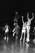 Elgin Baylor of the Minneapolis Lakers shoots against Swede Halbrook and Dave Gambee of the Syracuse Nationals circa 1959 at the Onondaga War...