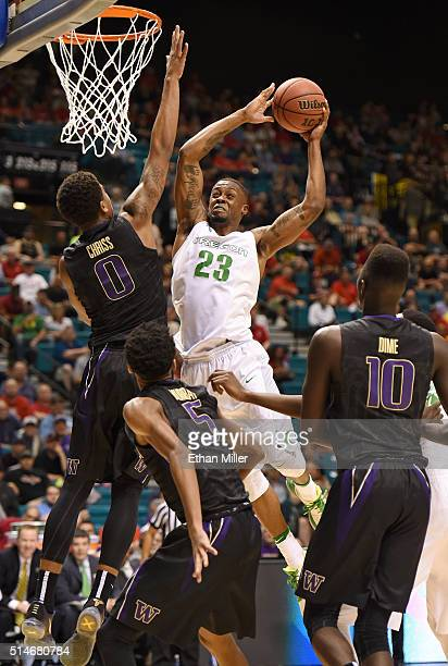 Elgin Cook of the Oregon Ducks drives to the basket against Marquese Chriss Dejounte Murray and Malik Dime of the Washington Huskies during a...