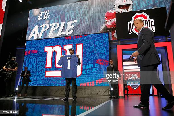 Eli Apple of Ohio State holds up a jersey after being picked overall by the New York Giants during the first round of the 2016 NFL Draft at the...