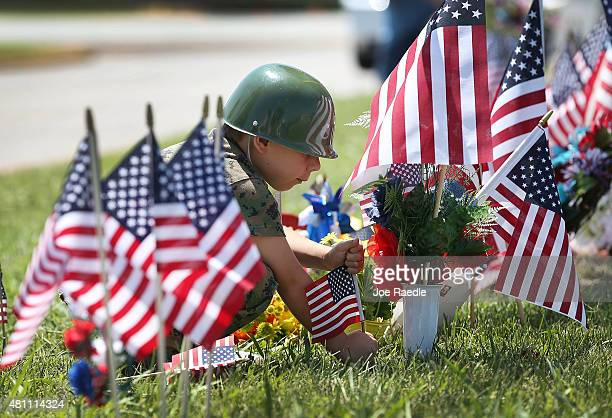 Eli Arnold places an American flag in the memorial in front of the Armed Forces Career Center/National Guard Recruitment Office which had been shot...