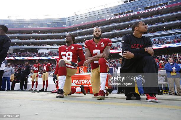 Eli Harold Colin Kaepernick and Eric Reid of the San Francisco 49ers kneel on the sideline during the anthem prior to the game against the Seattle...