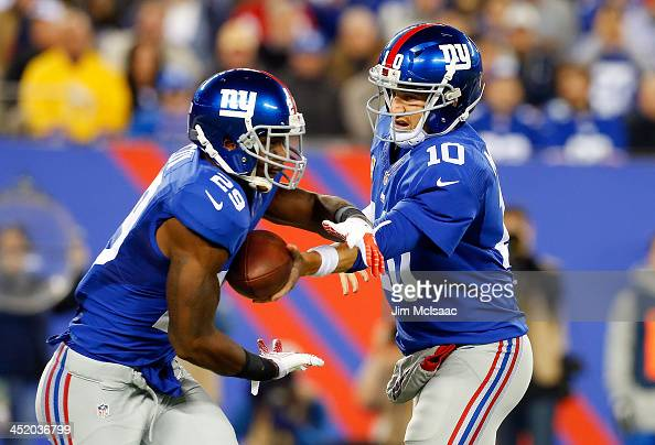 Eli Manning and Michael Cox of the New York Giants in action against the Minnesota Vikings on October 21 2013 at MetLife Stadium in East Rutherford...