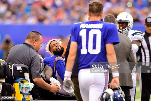 Eli Manning looks on as Odell Beckham of the New York Giants is taken off the field on a cart after sustaining an injury during the fourth quarter...