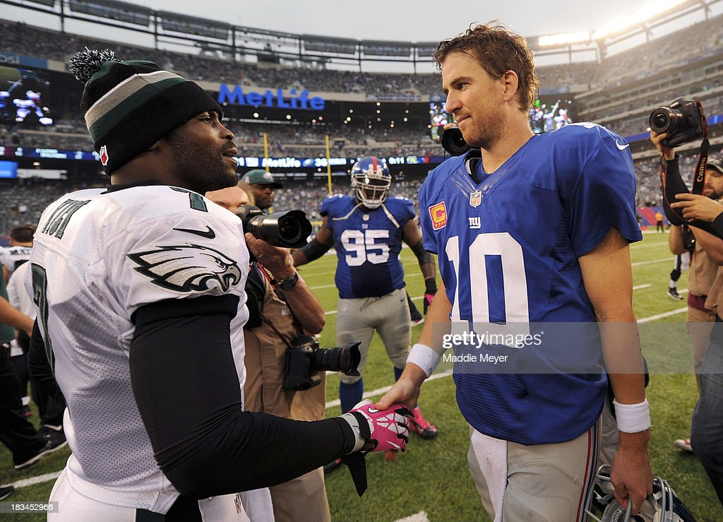 Eli Manning #10 of the New York Giants and Michael Vick #7 of the Philadelphia Eagles shake hands after the game at MetLife Stadium on October 6, 2013 in East Rutherford, New Jersey. The Eagles defeat the Giants 36-21.
