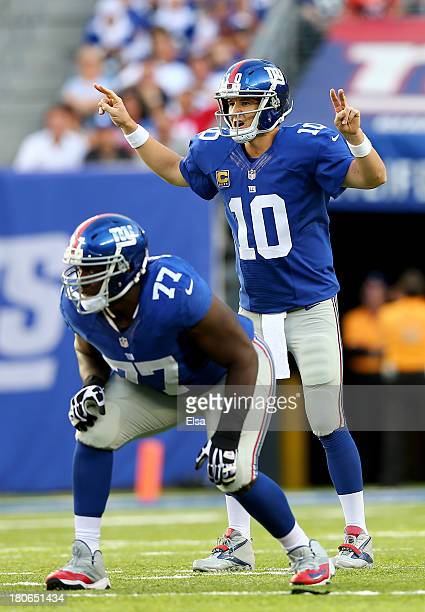 Eli Manning of the New York Giants calls out the play as teammate Kevin Boothe waits for the snap in the second quarter against the Denver Broncos at...