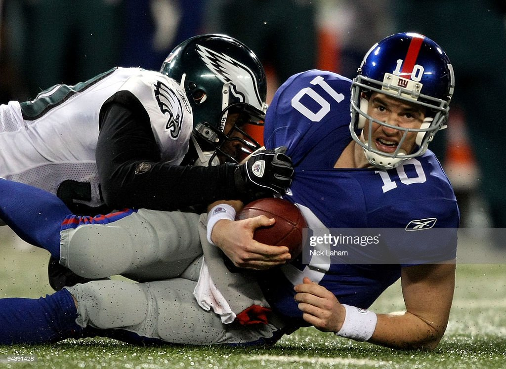 Eli Manning #10 of the New York Giants gets sacked late in the game by Will Witherspoon #50 of the Philadelphia Eagles at Giants Stadium on December 13, 2009 in East Rutherford, New Jersey.