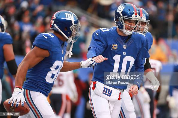 Eli Manning of the New York Giants high fives Victor Cruz of the New York Giants as they celebrate a touchdown against the Chicago Bears during the...