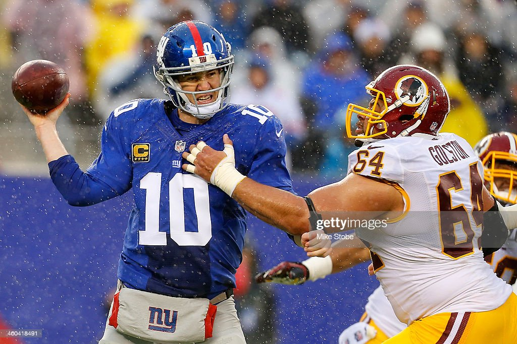 Eli Manning of the New York Giants is pressured by Kedric Golston of the Washington Redskins at MetLife Stadium on December 29 2013 in East...