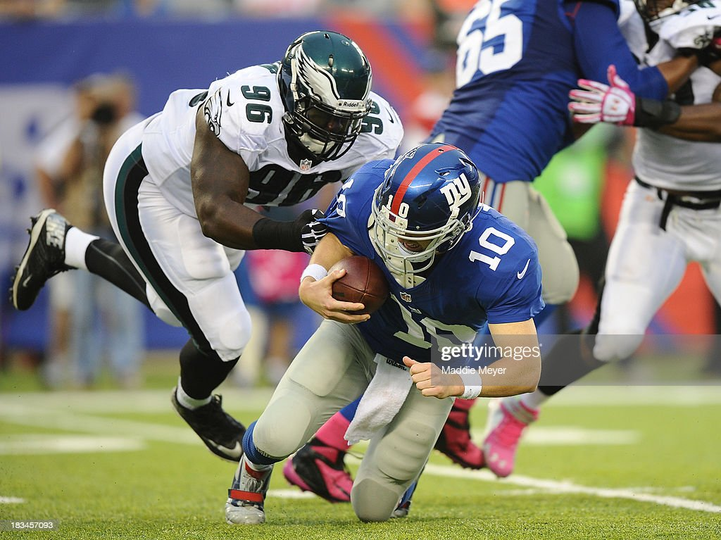Eli Manning #10 of the New York Giants is sacked by Bennie Logan #96 of the Philadelphia Eagles in the fourth quarter at MetLife Stadium on October 6, 2013 in East Rutherford, New Jersey. The Eagles defeat the Giants 36-21.