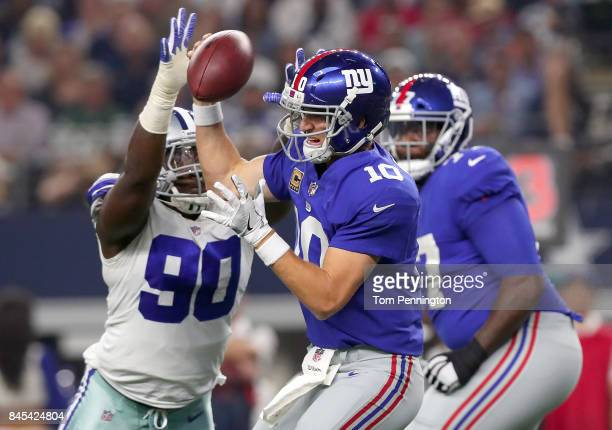 Eli Manning of the New York Giants is sacked for a loss by Demarcus Lawrence of the Dallas Cowboys in the first quarter at ATT Stadium on September...