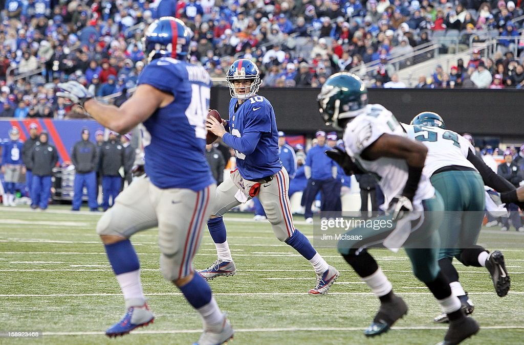 Eli Manning #10 of the New York Giants looks to throw a touchdown pass against the Philadelphia Eagles to teammate Henry Hynoski #45 at MetLife Stadium on December 30, 2012 in East Rutherford, New Jersey. The Giants defeated the Eagles 42-7.