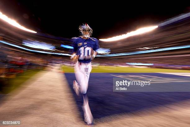 Eli Manning of the New York Giants runs off the field after warmups prior to the game against the Cincinnati Bengals at MetLife Stadium on November...