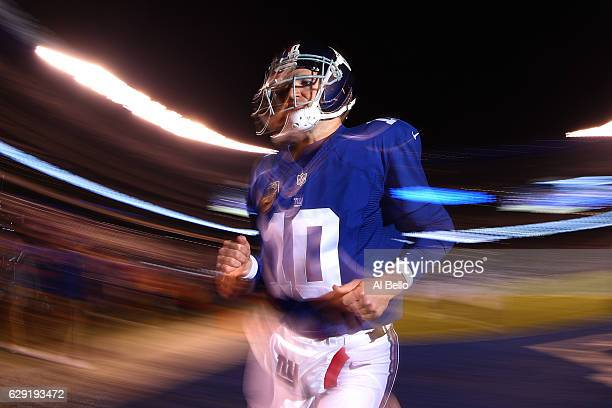 Eli Manning of the New York Giants runs off the field prior to the start of the game against the Dallas Cowboys at MetLife Stadium on December 11...
