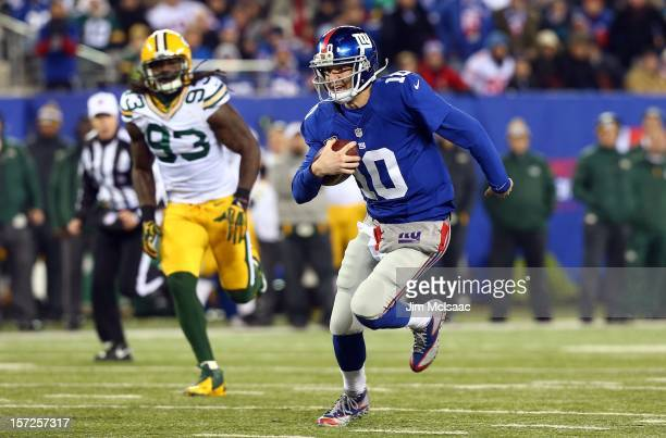 Eli Manning of the New York Giants runs the ball for a first down against the Green Bay Packers at MetLife Stadium on November 25 2012 in East...