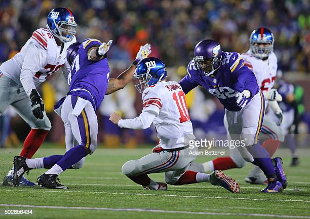 Eli Manning of the New York Giants takes a dive while Everson Griffen and Tom Johnson of the Minnesota Vikings go for the tackle in the second...