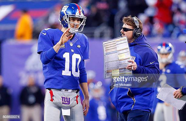 Eli Manning of the New York Giants talks with offensive coordinator Ben McAdoo during a game against the Carolina Panthers on December 20 2015 at...