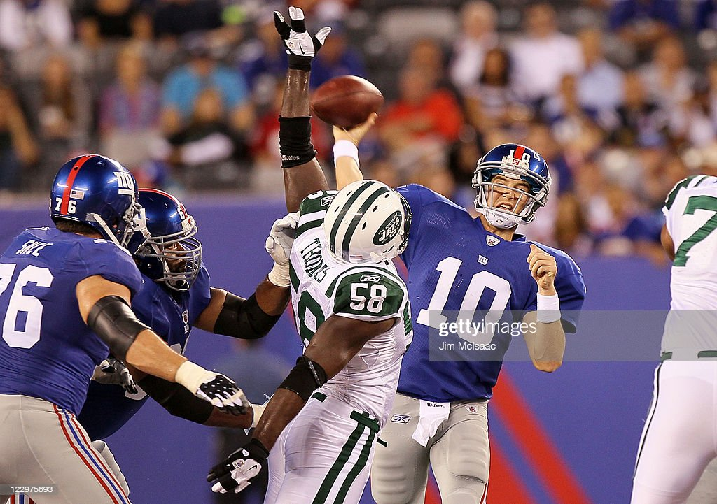 Eli Manning of the New York Giants throws a first half pass under pressure from Bryan Thomas of the New York Jets during their pre season game on...