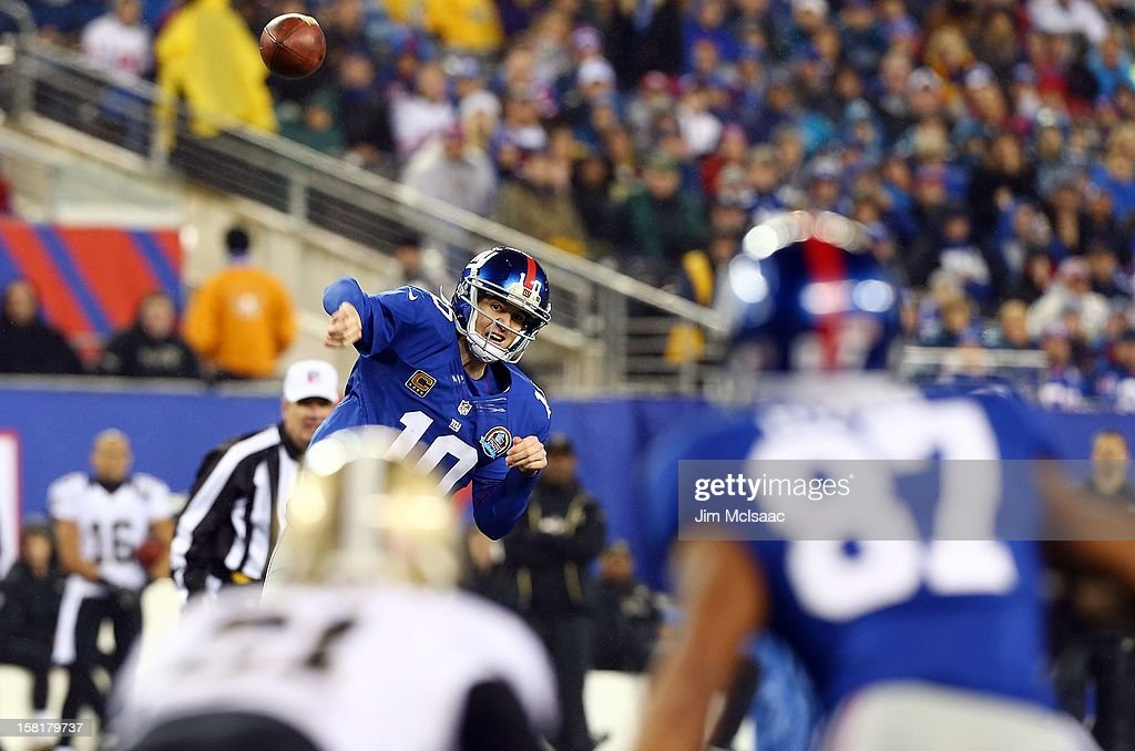 Eli Manning #10 of the New York Giants throws a pass against the New Orleans Saints to teammate Domenik Hixon #87 at MetLife Stadium on December 9, 2012 in East Rutherford, New Jersey. The Giants defeated the Saints 52-27.