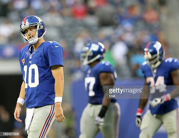 Eli Manning of the New York Giants walks off the field after throwing an interception in the fourth quarter against the Philadelphia Eagles at...