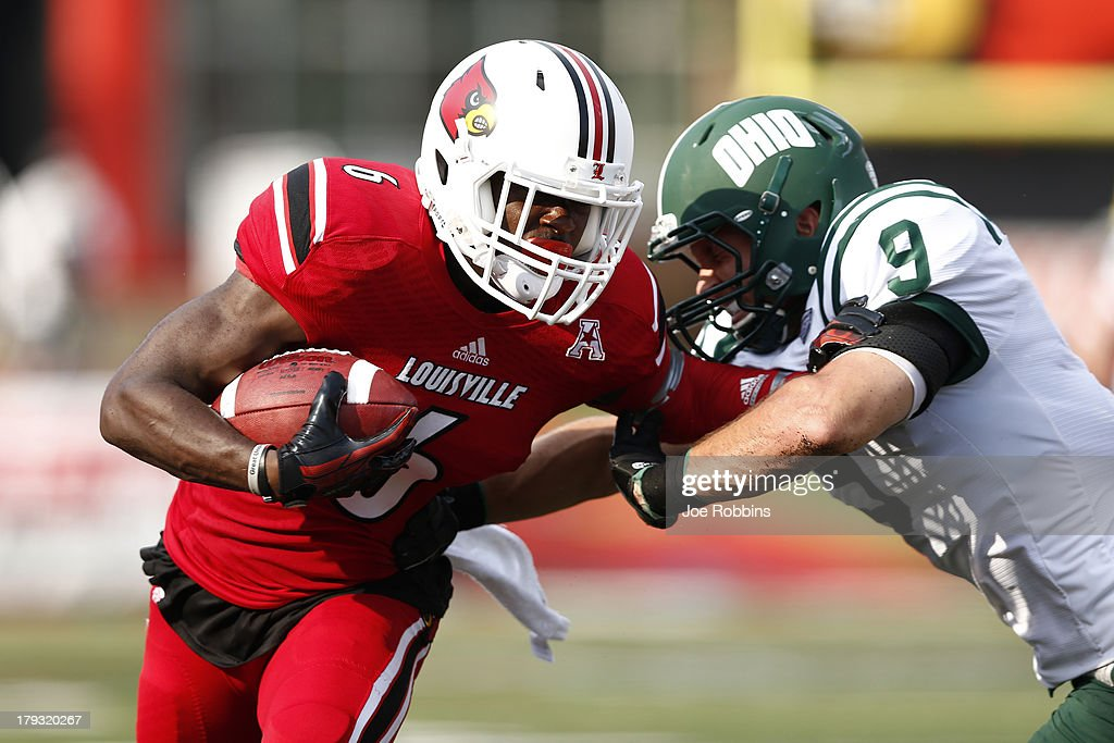 Eli Rogers #6 of the Louisville Cardinals tries to break a tackle after a reception against Josh Kristoff #9 of the Ohio Bobcats during the game at Papa John's Cardinal Stadium on September 1, 2013 in Louisville, Kentucky. Louisville won 49-7.