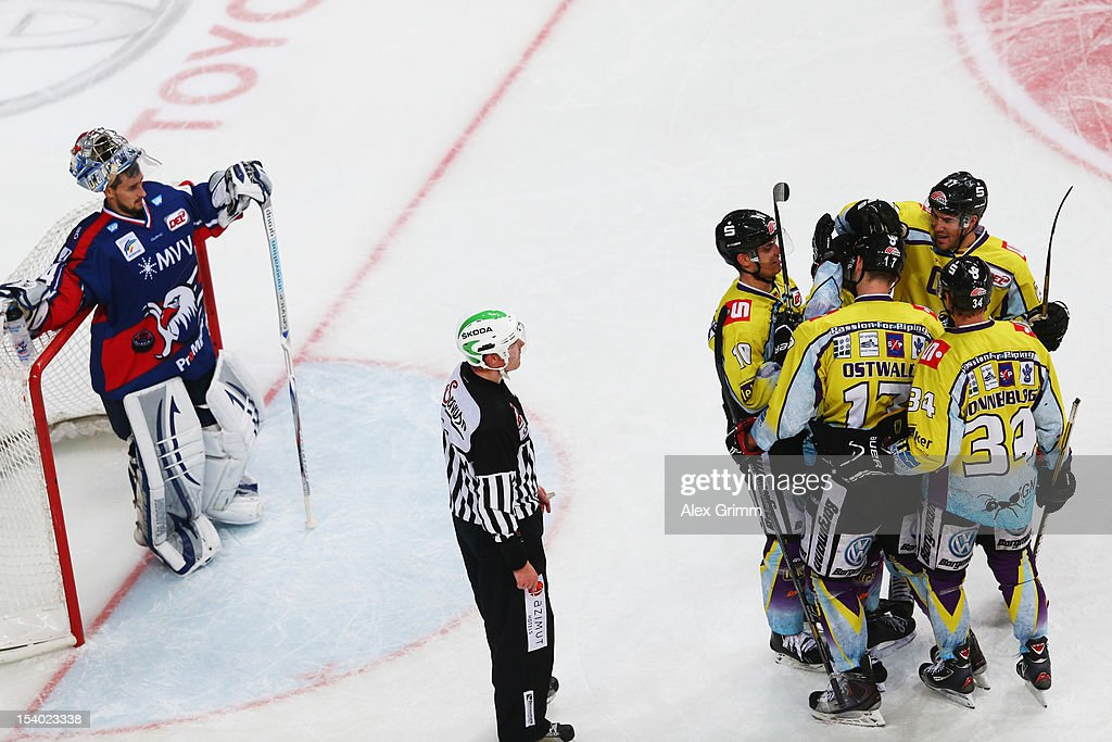 Elia Ostwald of Krefeld celebrates his team's fourth goal with team mates as goalkeeper <a gi-track='captionPersonalityLinkClicked' href=/galleries/search?phrase=Dennis+Endras&family=editorial&specificpeople=5526366 ng-click='$event.stopPropagation()'>Dennis Endras</a> of Mannheim reacts during the DEL match between Adler Mannheim and Krefeld Pinguine at SAP-Arena on October 12, 2012 in Mannheim, Germany.