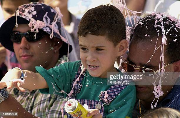 Elian Gonzalez sits on a friend's lap and plays with 'silly string' as he watches the Three Kings Parade 09 January in Miami's Little Havana Elian...